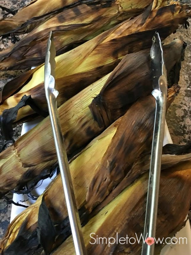corn in husk on grill with tongs