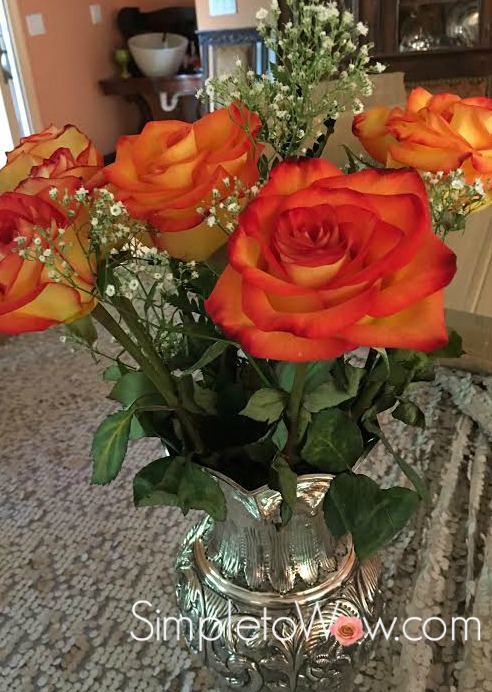 wilting roses in silver vase